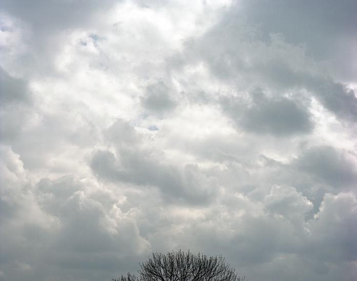 Foto einer dichten Wolkendecke mit den laublosen Spitzen eines Baumes am unteren Bildrand. Das Foto ist Teil des Projektes -Vollendete Gegenwart- des Kölner Fotografen Marcel Wurm.