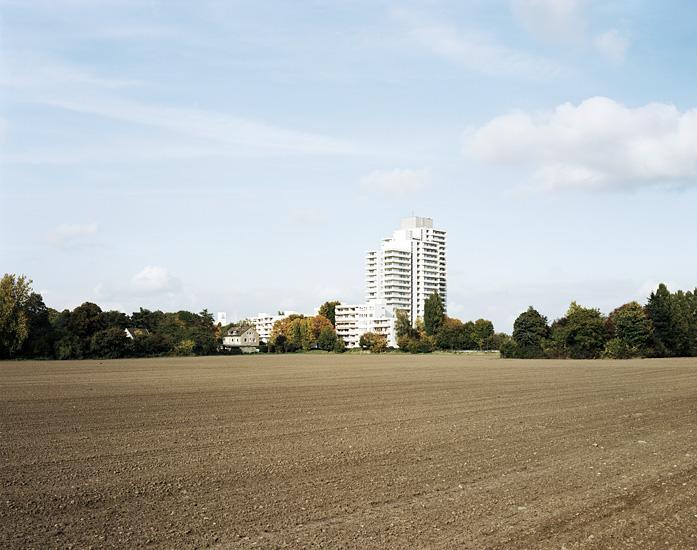 Foto eines Ackers mit Hochhaus am Horizont in Köln Poll. Fotografie angefertigt von Marcel Wurm für das Projekt -Vollendete Gegenwart-